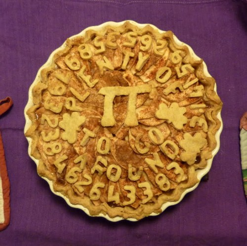 "In case you can't read it, it says ""Plenty of Pi to go around"" and has digits of pi arranged in a circle around the outside! Image and pie (c) Pippi, from this website."